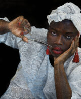 A portrait painting of Human Rights Activist Khadija Gbla. Khadija Gbla is wearing a white lace traditional African dress and headdress, bright read earrings, red lipstick and red nails. Her lips are stitched and she is holding a pair of scissors snipping open her sewn lips.